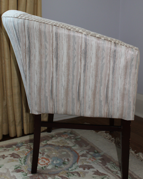 Side view of upholstered chair with stripped leather and fabric