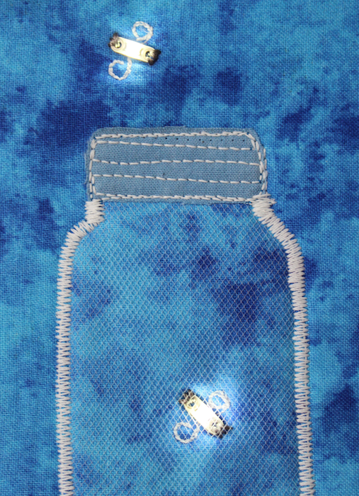 quilted art postcard with LED lights creating a mason jar filled with fireflies created by doris lovadina-lee in Toronto