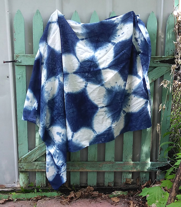 itajime shibori indigo dyed sarong draped on green picket fence toronto ontario canada