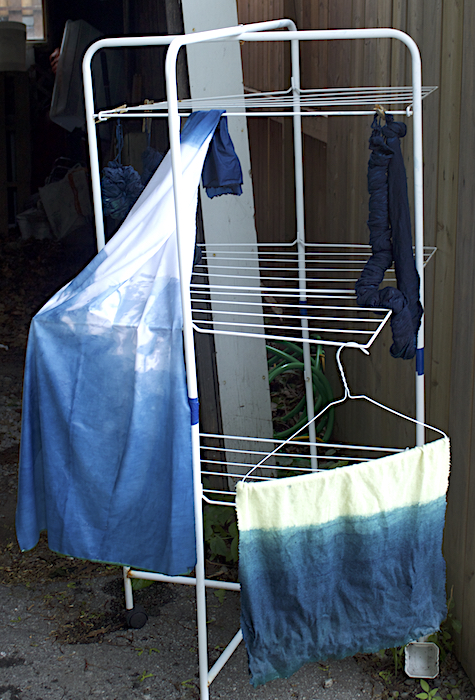 metal stand with two pieces of indigo dyed cloth hanging toronto ontario