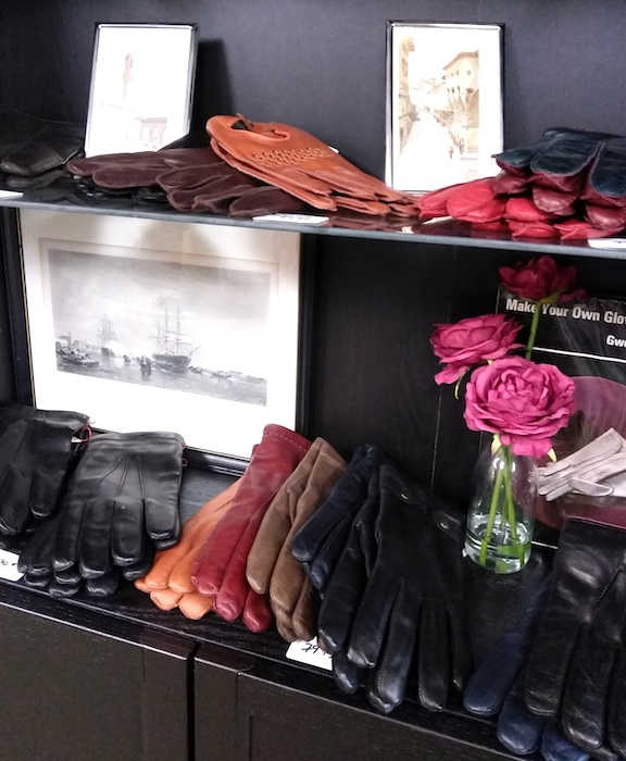glass display shelf with leather gloves, roses and photos in Boutique Firenze London