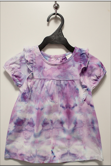 Ice dyed cotton top in purple hanging on black hanger