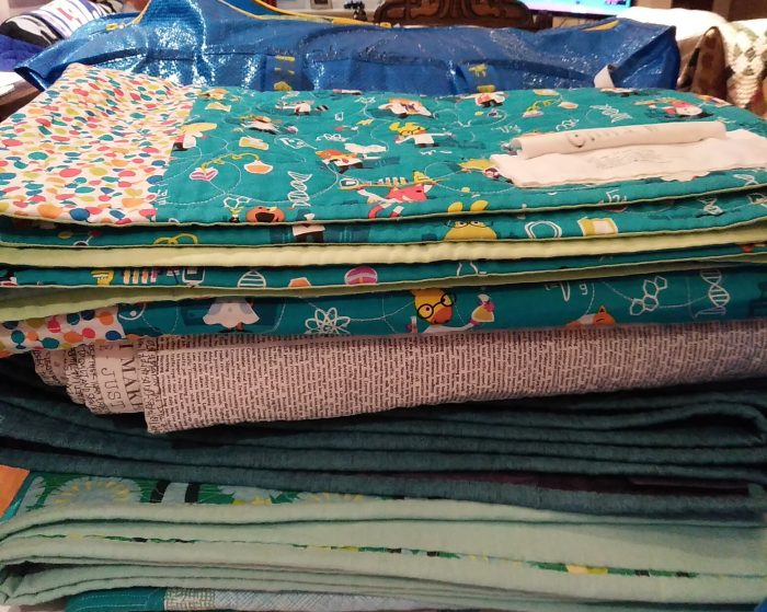 stacks of quilts for the show and share by doris lovadina-lee and Becky Burnett of the Toronto Modern Quilt guild october 2018