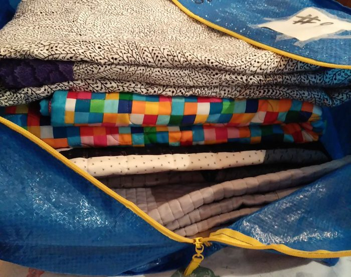 blue bag with quilts by members of the Toronto Modern Quilt Guild