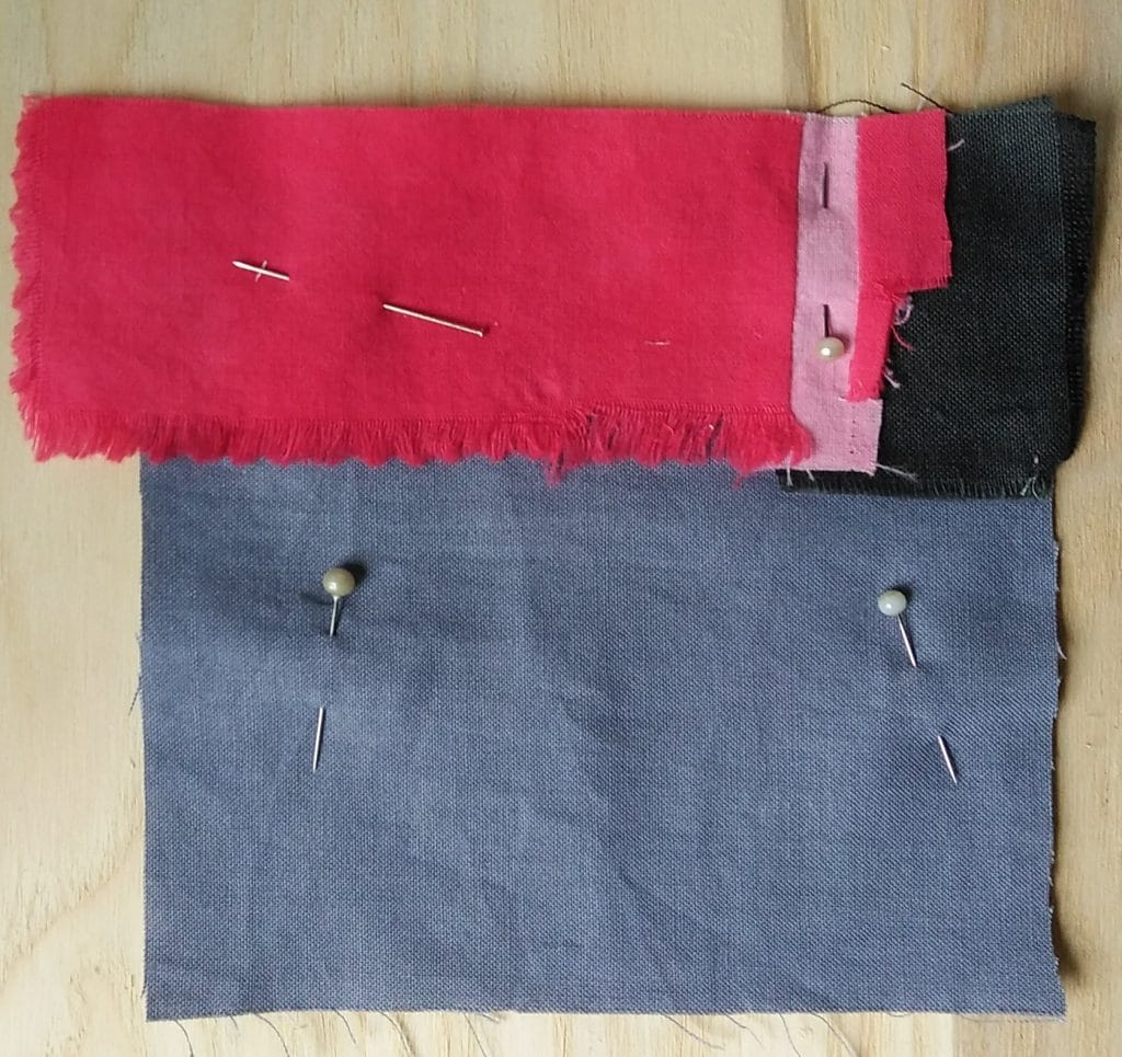 grey square with smaller red, pink and black patches on top held with pins