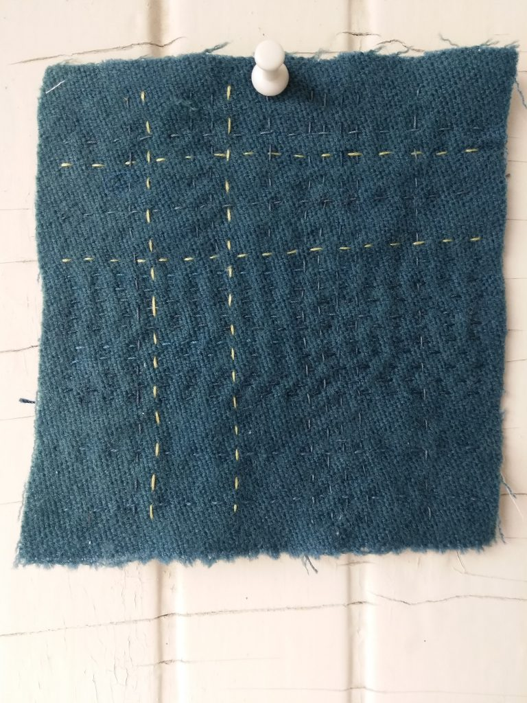 blue wool scquare embroidered with running stitches in hand dyed blue and yellow thread by doris lovadinalee canadian quilter