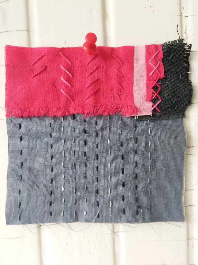 red, grey and black fabric held together with red and black embroidery stitches by doris lovadina-lee toronto artist