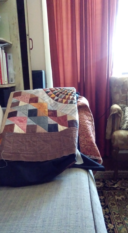 partially finished quilt draped on arm of sofa