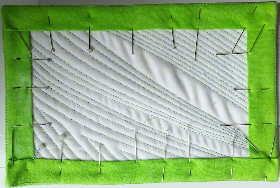 white quilt with green borders held with pins