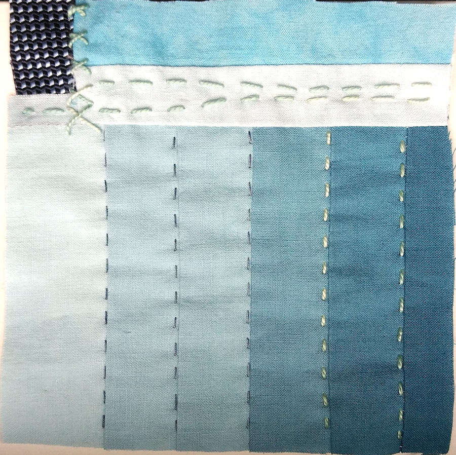 ombre shades of blue strips with hand stitching and one small darker square of silk in top left corner made by doris lovadina-lee canadian textile artist