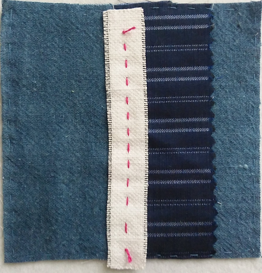 Indigo cotton and white linen 5 inch block held with red running stitch