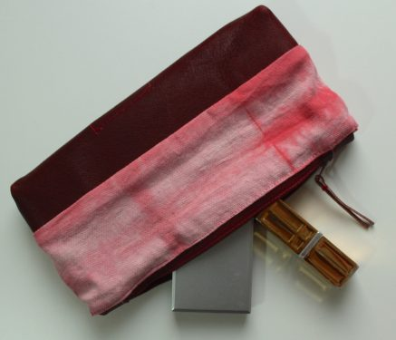 zippered pouch in burgundy hand dyed cotton and leather open with contents spilling out