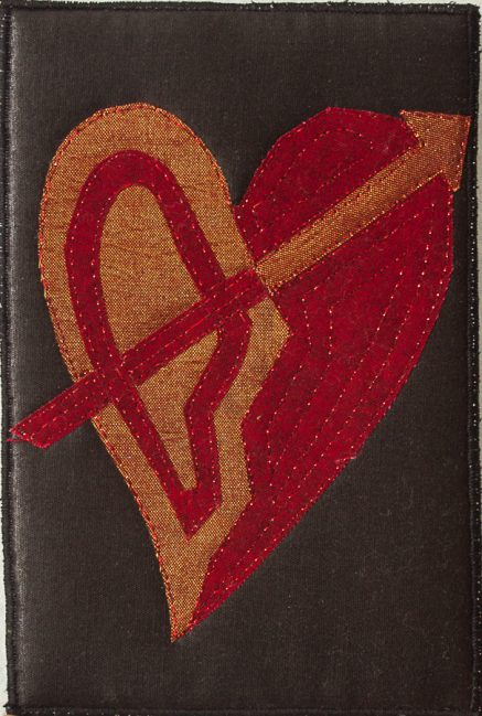 4 x 6 inch Red and gold metallic fabric heart pierced by an arrow on a shiny black fabric background