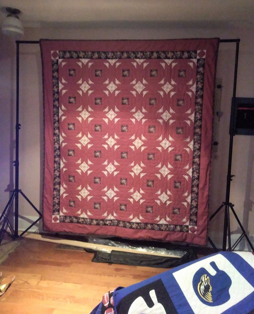 Roses and Lace is a large quilt hanging to be photographed by canadian artist doris lovadina-lee