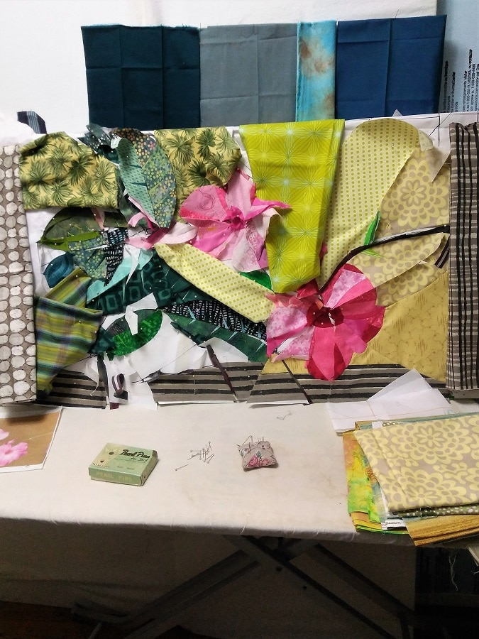 green, pink and yellow pieces of fabric layed out in flower design