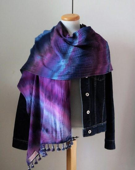 tasseled scarf draped around a jean jacket brightly colored in purple