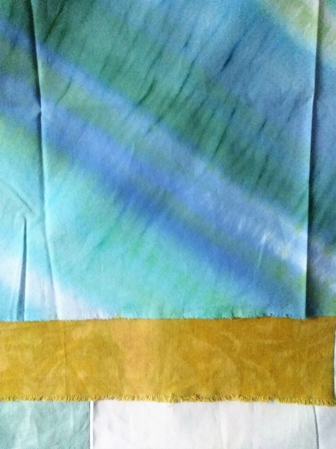 detail of hand dyed fabric showing rows of blue and turquoise
