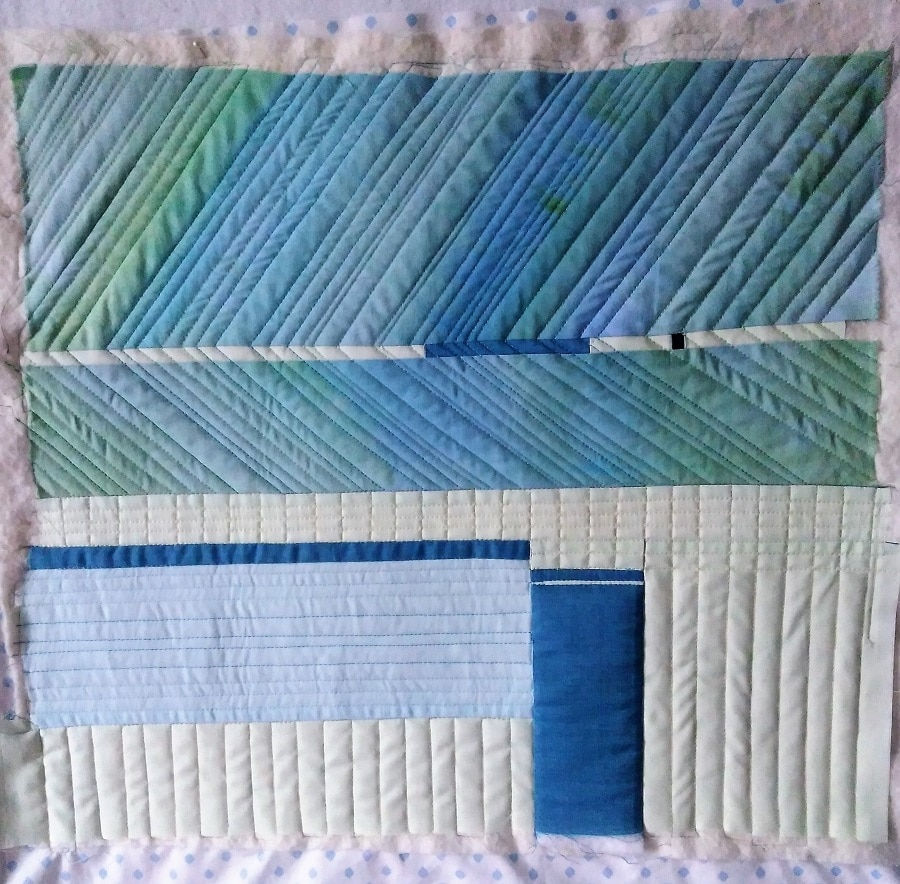 machine quilting on fabrics of blue and soft yellow