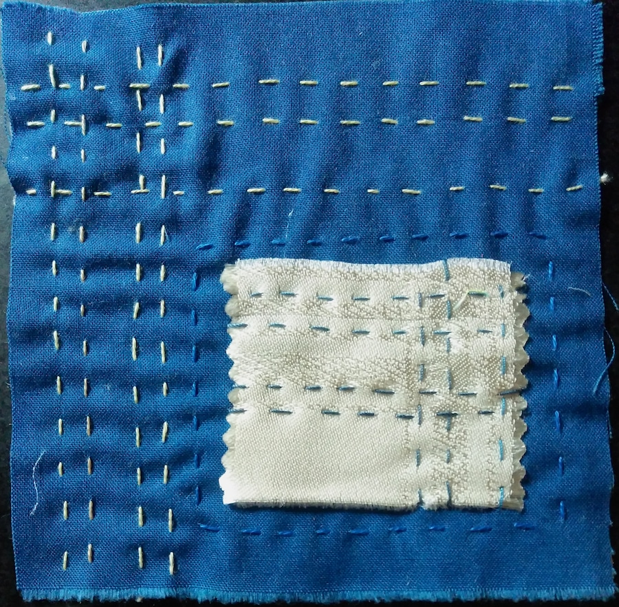 Stitch meditation day 87 made with a five inch blue cotton square and a small silk square embroidered with running stitches
